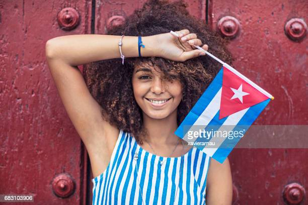 Portrait of woman holding Cuban flag against door