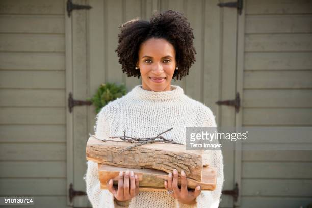 portrait of woman holding firewood - mid adult woman sweater stock pictures, royalty-free photos & images
