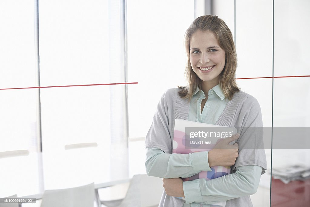 Portrait of woman holding folders in office : Stockfoto