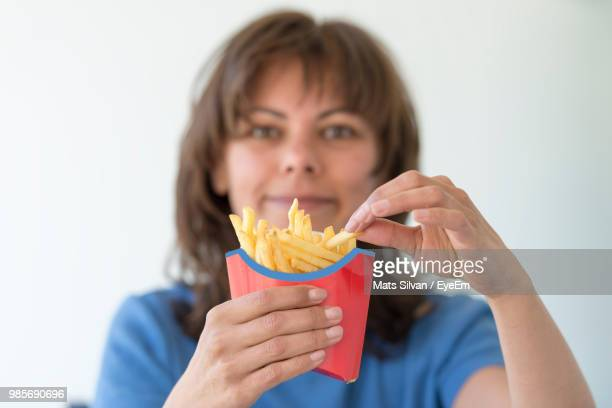 Portrait Of Woman Holding French Fries Against White Background