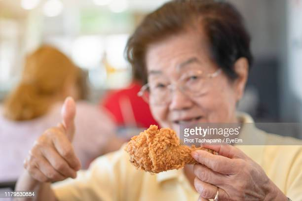 portrait of woman holding fried chicken and gesturing while sitting in restaurant - poulet frit photos et images de collection