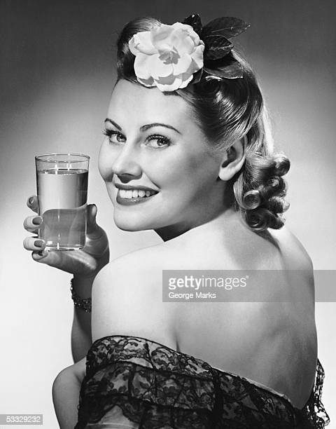 Portrait of woman holding glass of water
