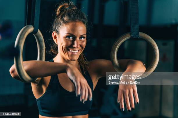 portrait of woman holding gymnastic rings - gymnastics poses stock pictures, royalty-free photos & images