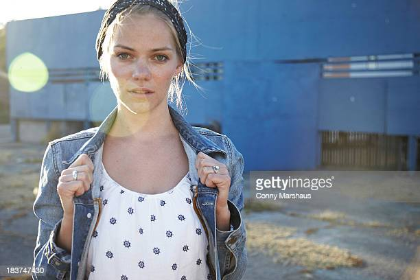 Portrait of woman holding jacket collar in industrial district