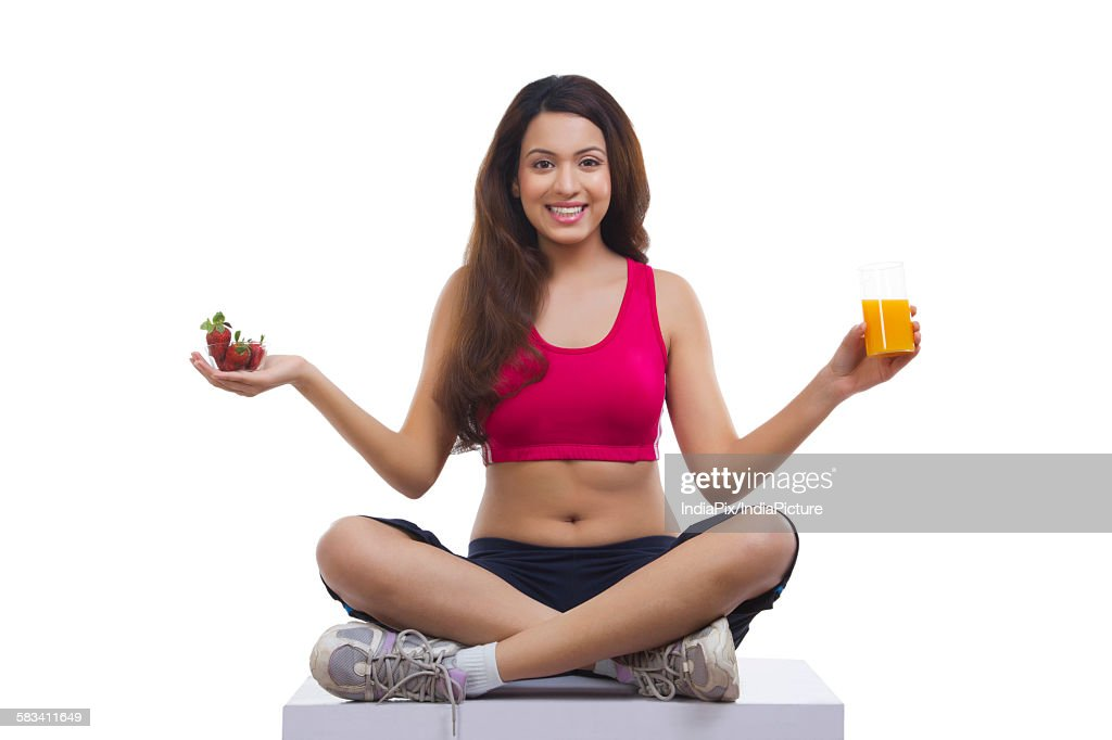 Portrait of woman holding juice and strawberry : Stock Photo