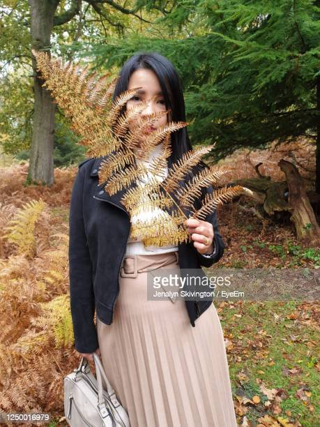 portrait of woman holding leaves while standing in forest - reality fernsehen stock pictures, royalty-free photos & images