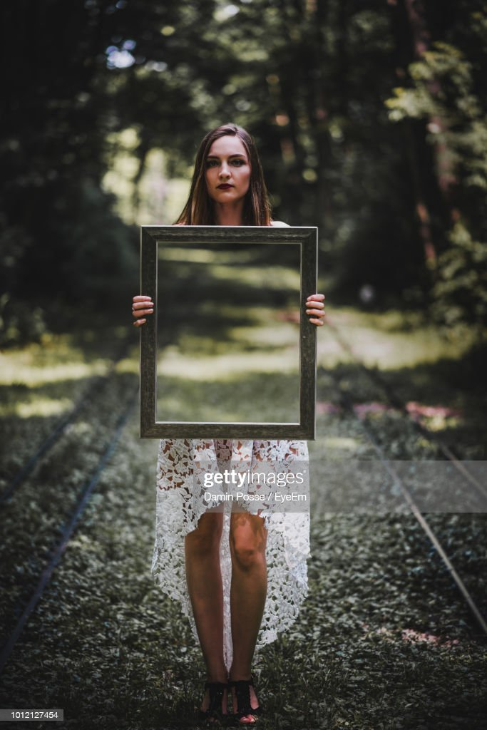 Woman Holding Mirror On Portrait Of Woman Holding Mirror While Standing On Footpath Stock Photo