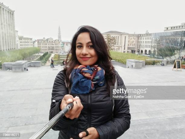 Portrait Of Woman Holding Monopod While Standing Against Buildings In City