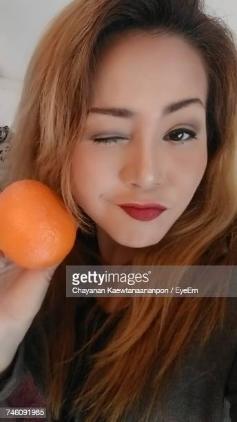 Portrait Of Woman Holding Orange With Winking Eye At Home
