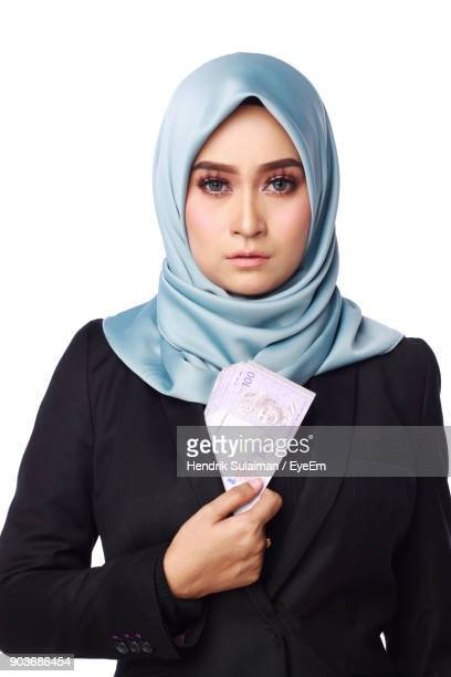 Portrait Of Woman Holding Paper Currency While Standing White Background