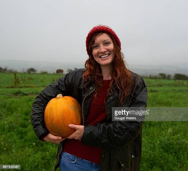 Portrait of woman holding pumpkin on farmland.
