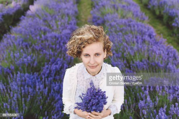 Portrait Of Woman Holding Purple Flowers