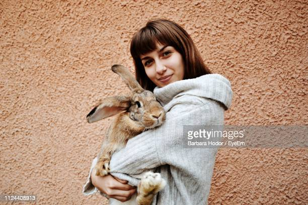 portrait of woman holding rabbit while standing by wall - lady barbara stock-fotos und bilder
