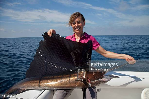 Portrait of woman holding sailfish on boat.