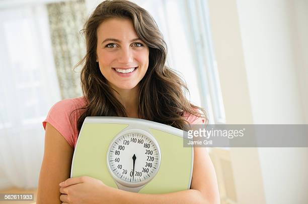 Portrait of woman holding scale
