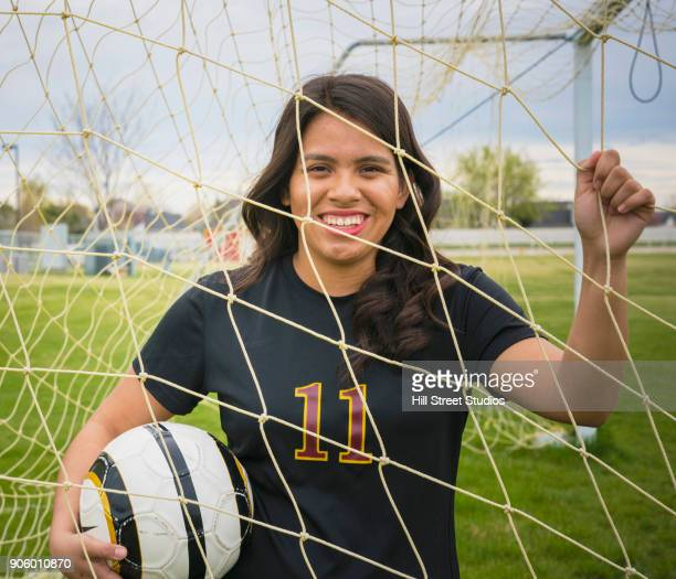 Portrait of woman holding soccer ball and net