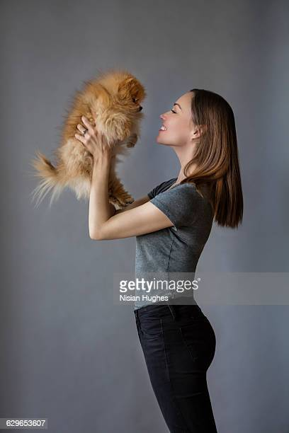 Portrait of Woman holding up her pet dog
