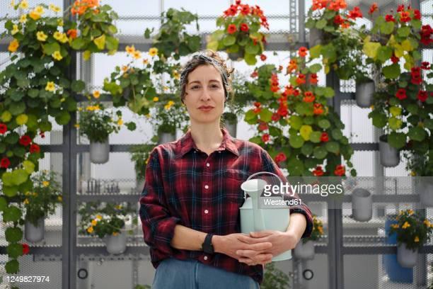 portrait of woman holding watering can in front of flowers in a gardening shop - schottenkaro stock-fotos und bilder