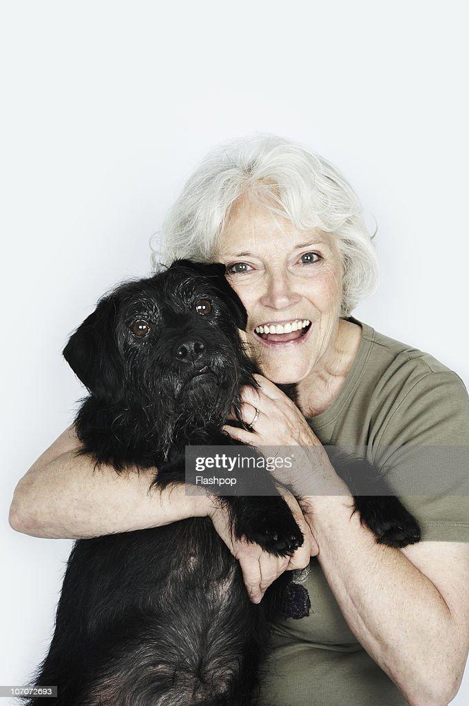 Portrait of woman hugging her pet : Stock Photo
