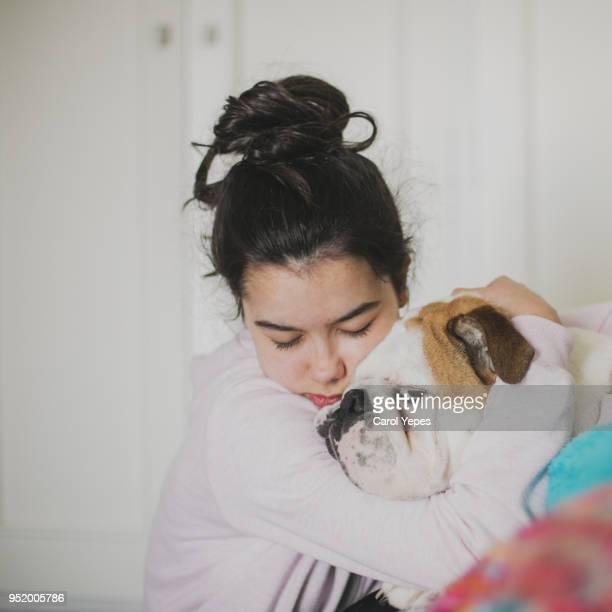 portrait of woman hugging pet - un animal fotografías e imágenes de stock