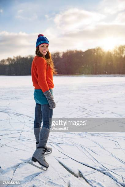 Portrait of woman ice skating on frozen lake
