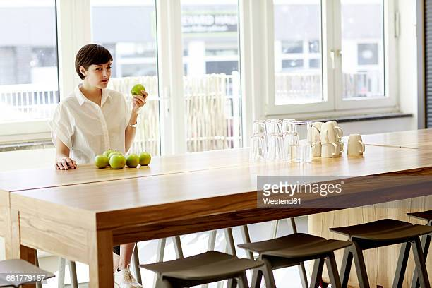 Portrait of woman in a modern canteen eating an apple
