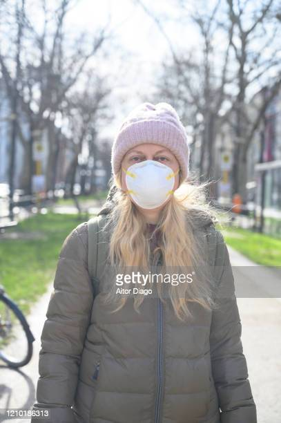 portrait of woman in a street wearing a protection mask looking at camera. berlin, germany. - 1918 flu pandemic stock pictures, royalty-free photos & images