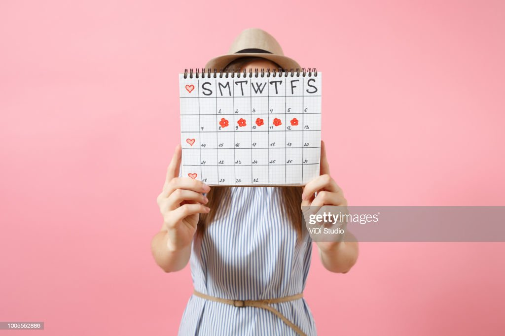 Portrait of woman in blue dress cover face, hiding behind periods calendar for checking menstruation days isolated on trending pink background. Medical, healthcare, gynecological concept. Copy space. : Stock Photo