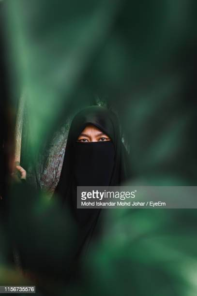 portrait of woman in burka by plants - burka stock pictures, royalty-free photos & images
