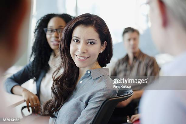 Portrait of woman in business meeting with colleagues