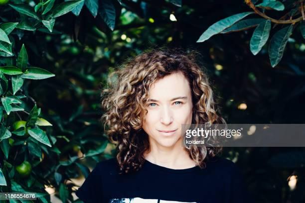 portrait of woman in citrus orchard - brune aux yeux bleus photos et images de collection