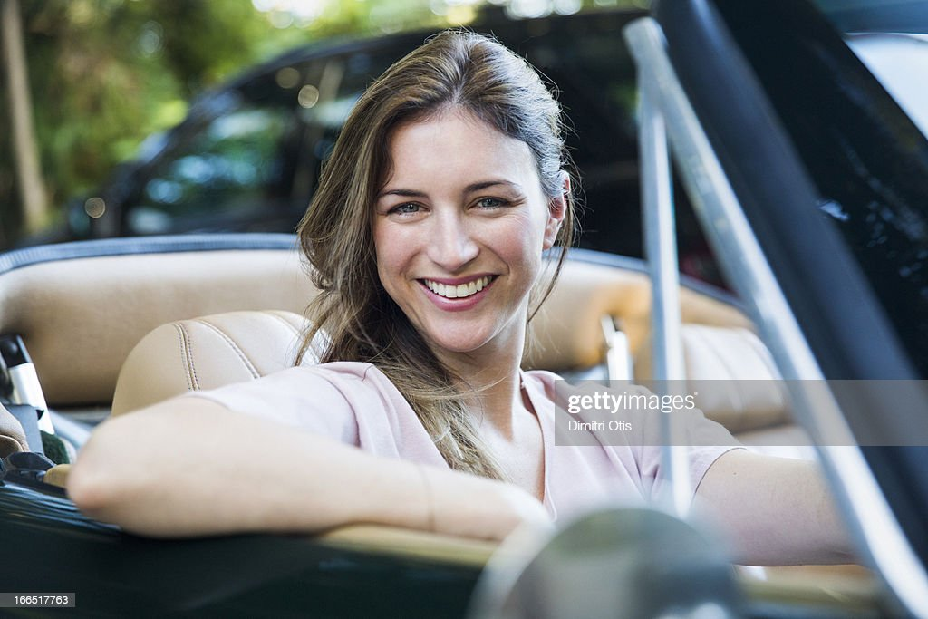 Portrait of woman in classic convertible car : Stock Photo