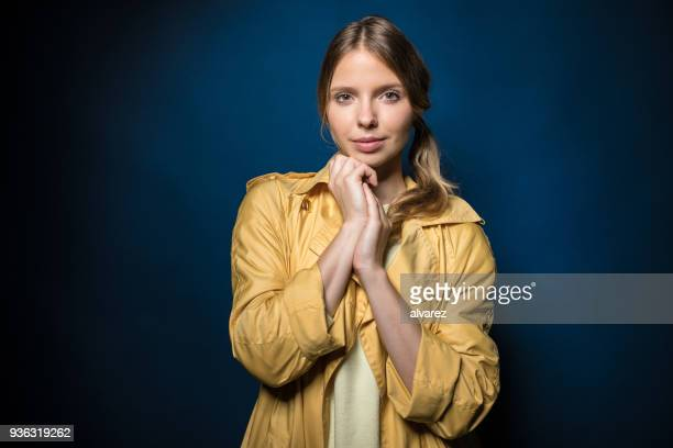 Portrait of woman in coat against blue background