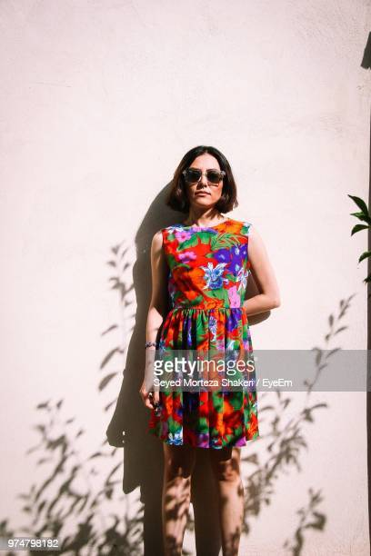 portrait of woman in colorful dress standing by wall - multi colored dress stock pictures, royalty-free photos & images