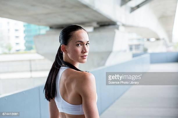 portrait of woman in crop top - mirar por encima del hombro fotografías e imágenes de stock
