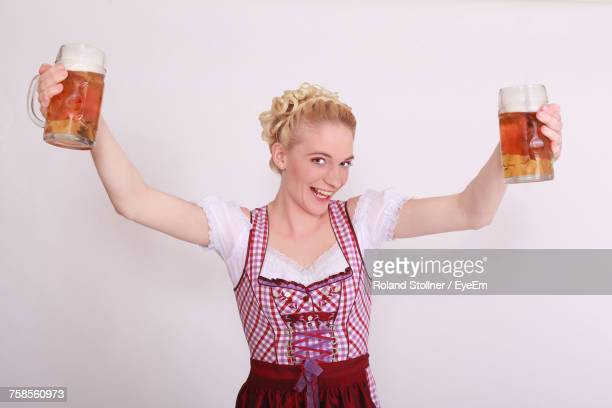 portrait of woman in dirndl holding beer glasses while standing against wall - german culture stock pictures, royalty-free photos & images