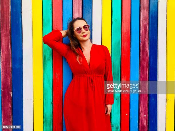 portrait of woman in dress standing against multi colored wall - lady madeleine stock-fotos und bilder