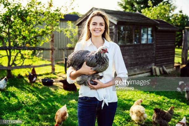 portrait of woman in early 20s holding free range chicken - west sussex stock pictures, royalty-free photos & images
