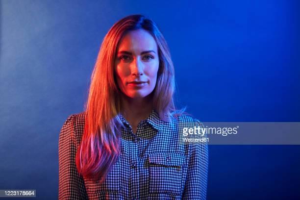 portrait of woman in front of a blue wall - farbbild stock-fotos und bilder