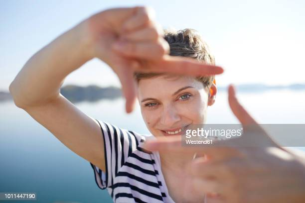 portrait of woman in front of lake shaping frame with her fingers - dedos fazendo moldura - fotografias e filmes do acervo