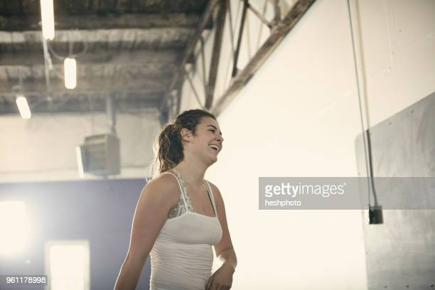 portrait of woman in gym looking away smiling - heshphoto stock pictures, royalty-free photos & images