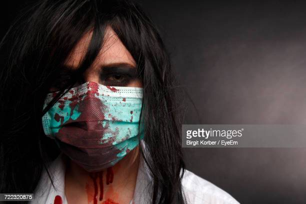 portrait of woman in halloween make-up against black background - eye black stock photos and pictures