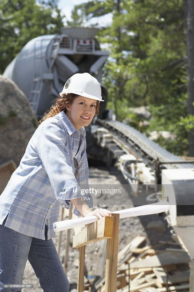 portrait of woman in hardhat on construction site stock photo