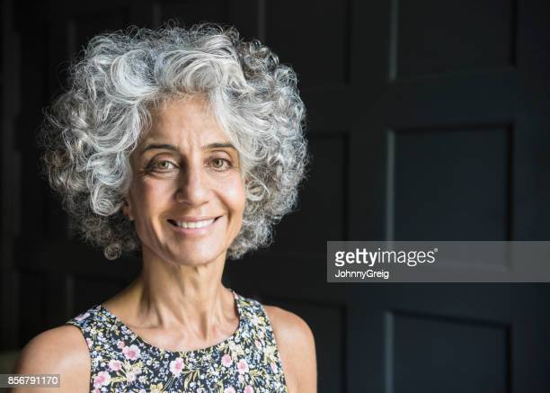 Retrato de mujer en sus 50s sonriendo a la cámara con vestido de flores sobre fondo oscuro