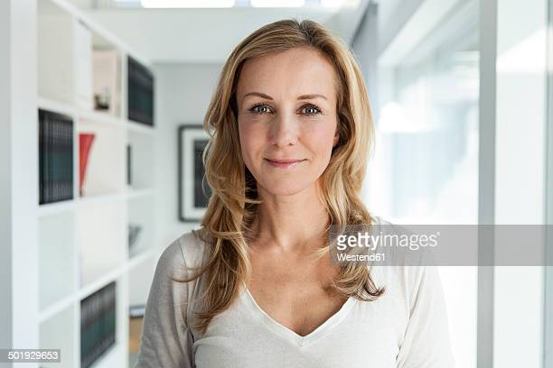 portrait of woman in her bright modern home - cheveux blonds photos et images de collection
