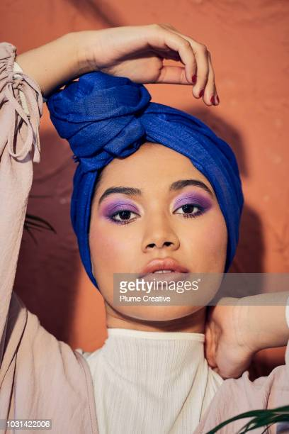 portrait of woman in hijab with hand on head - purple eyeshadow stock photos and pictures