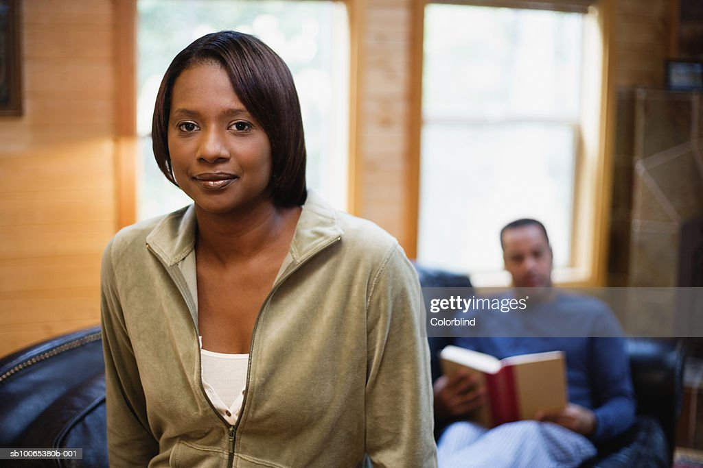 Portrait of woman in living room, out of focus man in background : Foto stock