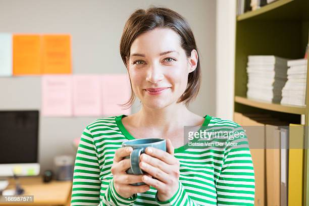 portrait of woman in office. - woman cradling mug stock pictures, royalty-free photos & images