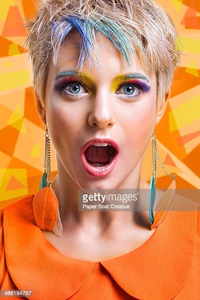 Portrait of woman in orange shirt looking shocked