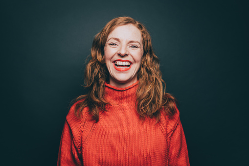 Portrait of woman in orange top laughing against gray background - gettyimageskorea